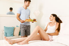 Breakfast in bed. Couple on a hotel room, and the men serving breakfast on bed Stock Image