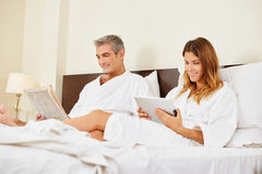 Couple in hotel room reading newspaper and tablet computer Stock Photos