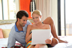 Couple in hotel room using laptop. Couple in hotel room connected on internet Stock Photo