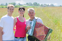 Couple hug near grandfather plays on accordion. Young couple hug near grandfather plays on accordion near village in field Royalty Free Stock Photos