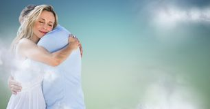 Couple hugging against blue green background with clouds Royalty Free Stock Photo
