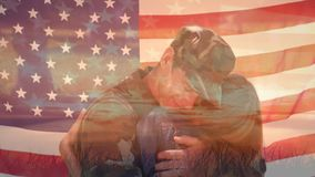 Couple hugging and American flag. Digital composite of a Caucasian man in military uniform hugging a Caucasian woman while foreground shows an American flag stock video