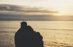 Couple hugging on background beach ocean sunrise, meeting of lovers concept, silhouette two romantic people cuddling and looking royalty free stock images