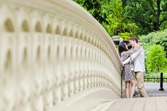Couple hugging in Central Park in New York City. Couple holding hands face to face on Bow Bridge in Central park in New York City royalty free stock photos