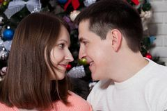 Young couple hugging over Christmas tree at home royalty free stock photos