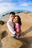 Couple hugging each other making funny face. Happy young couple hugging each other making funny face on the beach Stock Photography