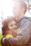 Couple hugging each other in sunlight. Couple of two young people in love hugging each other in the park in beautiful sunlight Royalty Free Stock Image