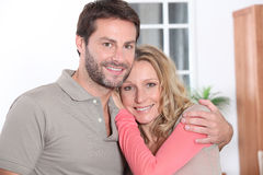 Couple hugging at home Stock Images