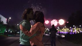 Couple hugging and kissing against fireworks. Slow motion. Couple hugging and kissing on the background of fireworks in night city