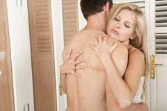 Couple hugging and kissing in bedroom. Stock Photo