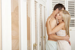 Couple hugging and kissing in bedroom. Royalty Free Stock Image