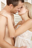 Couple hugging and kissing in bedroom. Royalty Free Stock Photo