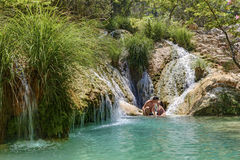 Couple hugging and kissing under waterfall Stock Images