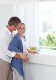 Couple hugging in the kitchen Stock Images