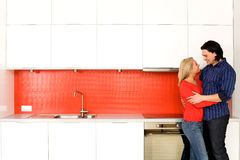 Couple hugging in kitchen Stock Photo