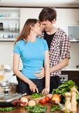 Couple hugging in the kitchen. While cooking Stock Photo