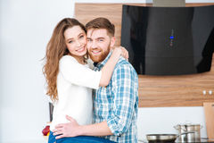 Couple hugging and looking at camera. Smiling young couple hugging and looking at camera Stock Images