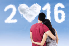 Couple hugging while looking at numbers 2016 Stock Photo
