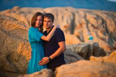 Couple hugging in the middle of large boulders on the sea background royalty free stock images