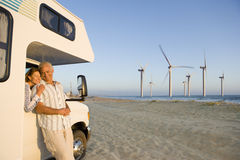 Couple hugging by motor home with wind turbines in distance Stock Image
