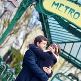 Couple hugging near a subway station in Paris Stock Photo