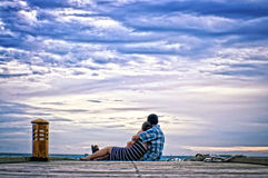 Couple hugging on a pier. A couple embracing and sitting on a pier, looking out to sea with an overcast sky, hint of blue shining through Stock Photos