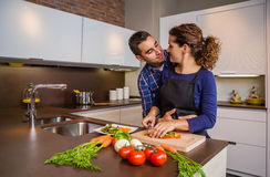 Couple hugging and preparing vegetables in the Royalty Free Stock Image