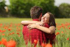 Couple hugging after proposal in a flower field. Happy couple hugging affectionate after proposal in a green field with red flowers royalty free stock image
