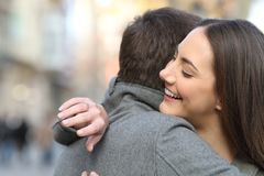 Couple hugging after proposal and girlfriend looking at ring. Couple hugging after marriage proposal and girlfriend looking at engagement ring in the street stock image