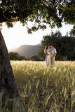 Couple hugging in rural field stock photography