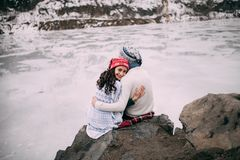 Couple is hugging and smiling against background of frozen lake. Girl looks back. royalty free stock image