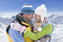 Couple hugging in snow with mountain in background Stock Photos