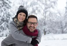Couple hugging on snow. Portrait of happy young couple hugging on snow in forest stock image