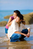 Couple hugging and squating at the beach. Loving young couple hugging and squatting at the beach Royalty Free Stock Image