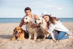 Couple hugging three dogs and sitting on the beach Royalty Free Stock Photography