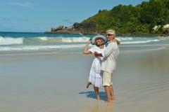Couple hugging  on  tropical beach. Happy elderly couple  hugging  on  tropical beach Stock Images