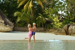 Couple hugging  on  tropical beach. Happy elderly couple  hugging  on  tropical beach Royalty Free Stock Photos
