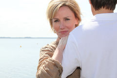 Couple hugging by the water Stock Photo