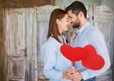The couple hugs with hearts in their hands indoors. Valentine`s Day Royalty Free Stock Photos