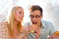 Couple is hungry and eating a burger at break. Couple is hungry and eating a burger at lunch time in the sun Stock Images