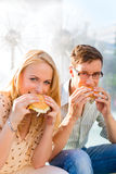 Couple is hungry and eating a burger at break Royalty Free Stock Image