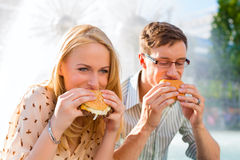 Couple is hungry and eating a burger at break. Couple is hungry and eating a burger at lunch time in the sun Royalty Free Stock Images