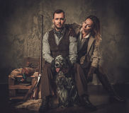 Couple of hunter with a english setter and shotgun in a traditional shooting clothing, sitting on a dark background. Stock Photo