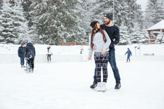 Couple in ice skates hugging and looking at each other. Happy couple in ice skates hugging and looking at each other outddors with snow on background Stock Photos