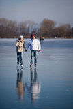 Couple ice skating outdoors on a pond Stock Image