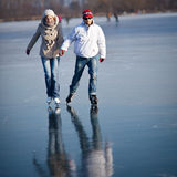 Couple ice skating on a pond. Couple ice skating outdoors on a pond on a lovely sunny winter day Stock Photos