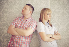 Couple ignoring each other after an argument. Standing facing away from one another with serious disgruntled expressions , against retro patterned beige Royalty Free Stock Photo
