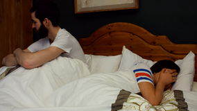Couple ignoring each other on bed in bedroom stock video