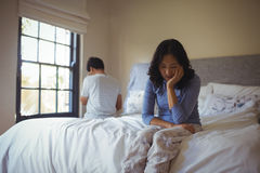 Couple ignoring each other in bedroom Stock Images