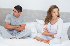 Couple ignoring each other. Mid adult couple ignoring each other in bed Royalty Free Stock Images